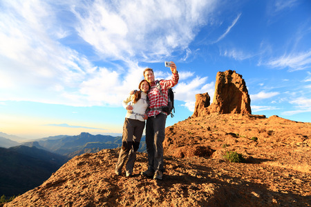 canary islands: Couple taking selfie hiking in beautiful nature with smart phone. Happy couple walking enjoying view and taking pictures with smartphone. Man and woman by Roque Nublo, Gran Canaria, Canary Islands. Stock Photo