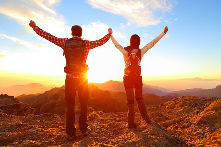 trekking: Freedom - Happy couple cheering and celebrating. Hiking man and woman raising arms excited in celebration outdoors. Hikers at sunset in mountain enjoying mountain top summit and success.
