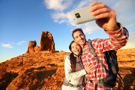 senderismo: Selfie - Pareja feliz tomando fotos de auto retrato senderismo. Dos amigos o amantes en alza sonriendo a la c�mara al aire libre monta�as por Roque Nublo, Gran Canaria, Islas Canarias, Espa�a. Foto de archivo