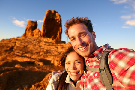 canaria: Happy couple taking selfie self-portrait photo hiking. Two friends or lovers on hike smiling at camera outdoors mountains by Roque Nublo, Gran Canaria, Canary Islands, Spain. Stock Photo