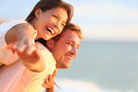 Strand paar lachen in liefde romantiek over reizen huwelijksreis vakantie zomervakantie romantiek. Jonge gelukkige mensen, Aziatische vrouw en blanke man omhelzen, buitenshuis op tropisch strand in vrijetijdskleding.