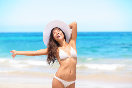 Woman on beach enjoying sun happy on travel smiling under blue sky. Cheerful beautiful bikini girl sun tanning having fun on tropical beach. Fresh laughing mixed race Asian Caucasian model on holidays