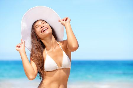Gelukkige vrouw op het strand genieten van zon lachend onder blauwe hemel. Vrolijke mooie bikini meisje zonnen plezier op tropisch strand. Verse lachende gemengd ras Aziatische Kaukasische model op vakantiereizen.