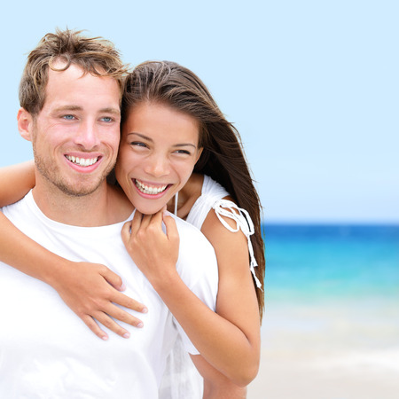 Beach couple lovers on romantic travel in love on honeymoon vacation summer holidays romance. Young happy people, Asian woman and Caucasian man embracing outdoors on tropical beach in casual wear. photo