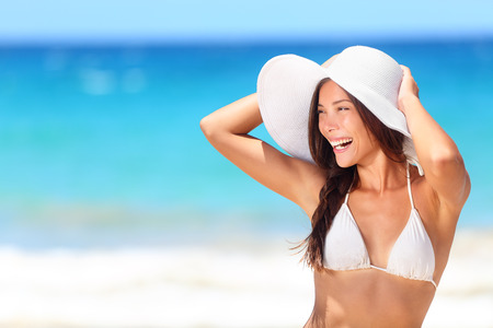 Beach woman happy smiling laughing lifestyle. Bikini girl wearing sun hat looking to side at copy space excited at joyful. Beautiful sexy mixed race woman having fun on summer travel vacation.