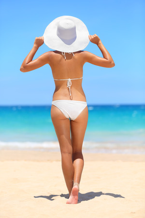Woman on beach travel vacation lifestyle concept. Bikini girl looking at ocean sea view wearing sun hat on holidays under blue clear summer sky on tropical beach in full body length rear back view.