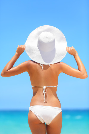 Beach woman travel vacation lifestyle concept. Bikini girl looking at ocean sea view wearing sun hat enjoying holidays under blue clear summer sky on tropical beach.
