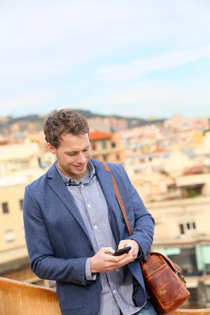 male fashion model: Hombre de negocios urbano Profesional joven que usa smartphone mediante mensaje sms aplicaci�n de mensajes de texto en el tel�fono inteligente llevaba traje chaqueta de moda en Barcelona, ??Catalu�a, Espa�a. Modelo de moda masculina de raza cauc�sica. Foto de archivo