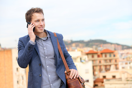 Man op smartphone - jonge zakenman praten op slimme telefoon. Casual stedelijke professionele zakenman met behulp van mobiele telefoon lacht graag wandelen. Knappe man dragen pak jas in Barcelona, Spanje Stockfoto