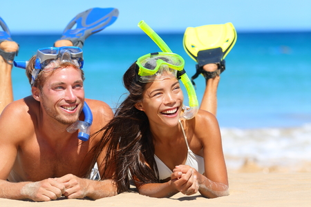 snorkel: Beach travel couple having fun snorkeling. Happy young multiracial couple lying on summer beach sand with snorkel equipment looking to side at copy space after swimming with fins and mask on vacation.
