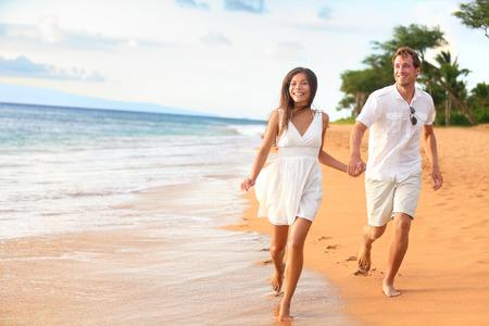 로맨틱 한 여행 신혼 여행 휴가 여름 휴가 로맨스에서 실행 재미에 비치 커플 산책. 행복 한 젊은 연인, 야외에서 손을 잡고 아시아 여자와 백인 남자.