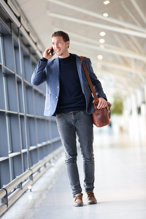 Urban business man talking on smart phone traveling walking in full body length inside in airport. Casual young businessman wearing suit jacket and shoulder bag. Handsome male model in his 20s. Stock Photo