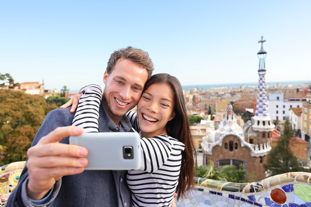 Travel couple happy talking selfie self-portrait with smartphone in Park Guell, Barcelona, Spain. Beautiful young multiracial couple looking at camera taking photo with smart phone smiling in love. photo