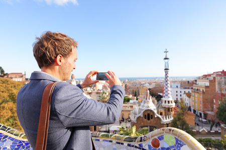 Tourist man taking photo in with smartphone in Park Guell, Barcelona, Spain. Young professional business man sightseeing taking picture with smart phone in Spain, Europe.