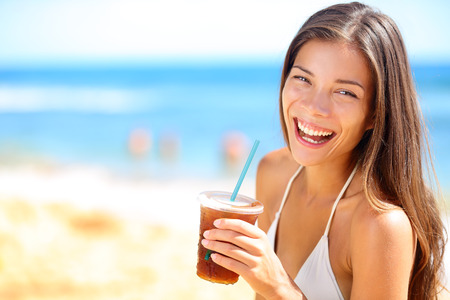coke: Beach woman drinking cold drink beverage having fun at beach party. Female babe in bikini enjoying Ice tea, coke or alcoholic drink smiling happy laughing looking at camera. Beautiful mixed race girl Stock Photo