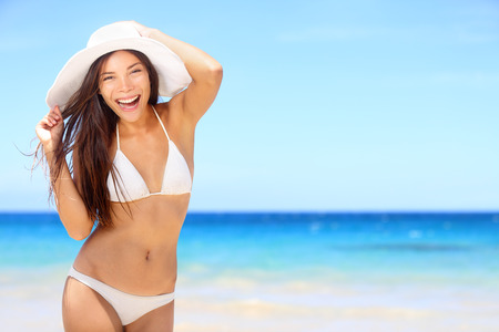 girl woman: Beach woman happy on travel vacation holidays in bikini on by blue ocean sea at tropical resort. Cheerful smiling excited mixed race girl wearing sun hat laughing full of joy looking at camera.