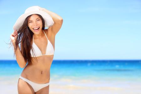 Strand vrouw gelukkig op vakantie vakantie in bikini op door blauwe oceaan zee op tropische resort. Vrolijke glimlachende enthousiast gemengd ras meisje dragen zonne hoed lachen vol vreugde kijken naar de camera.