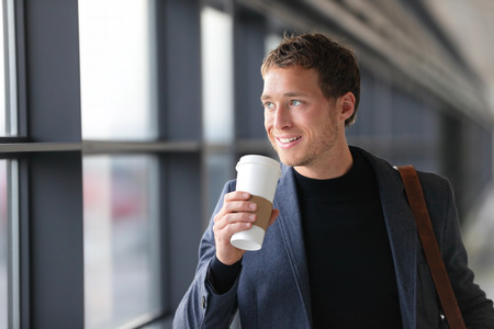 drinking coffee: Businessman drinking coffee walking in airport. Casual urban professional smiling happy wearing suit jacket holding disposable coffee cup on travel. Handsome male model in his twenties.