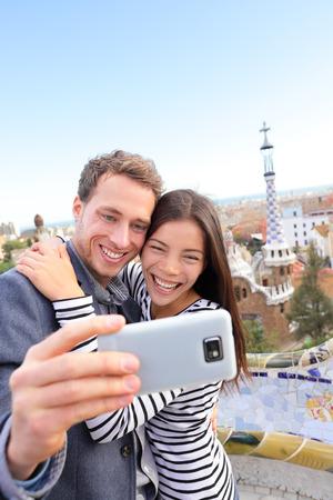 Barcelona: Couple Voyage heureux de parler selfie auto-portrait avec le smartphone dans le parc Guell, Barcelone, Espagne. Belle jeune couple multiracial regardant la caméra photo prise avec un téléphone intelligent souriant dans l'amour.