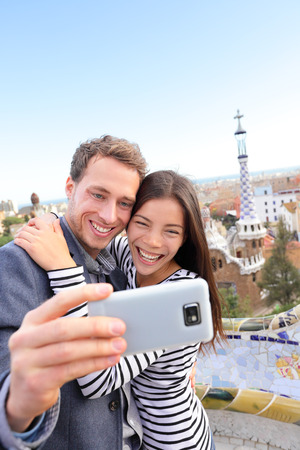 Happy travel couple talking selfie self-portrait with smartphone in Park Guell, Barcelona, Spain. Beautiful young multiracial couple looking at camera taking photo with smart phone smiling in love.