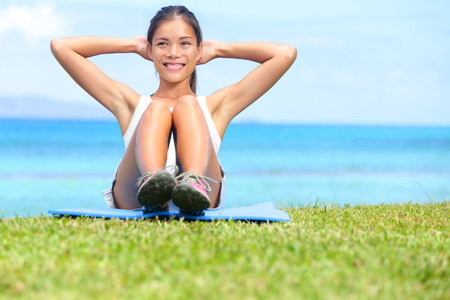 Exercise woman doing situps in outdoor workout training in grass on beach. Asian sport fitness woman smiling cheerful and happy doing situps crunches as part of strength training and healthy lifestyle photo