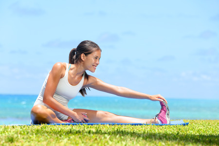 Woman stretching legs exercise training fitness outside by the ocean sea. Beautiful fit female fitness girl model sitting on grass doing stretch exercising after workout. Mixed race Asian female model Stock Photo