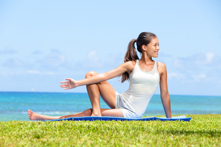 Woman stretching legs in yoga exercise fitness training outside by the ocean sea. Beautiful fit female girl model sitting on grass doing stretch exercising after workout. Mixed race Asian female model