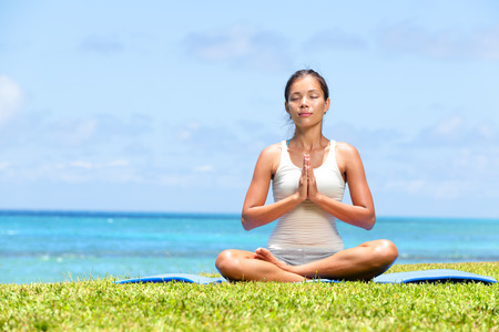 Meditation yoga woman on beach meditating by ocean sea sitting in lotus position with back turned serene and happy. Asian girl sitting relaxing enjoying summer beach. Mixed race Asian Caucasian model.