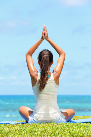 Meditation yoga woman meditating at beach relaxing in yoga pose. Serene relaxed female yoga instructor in calm nature sea scene. photo