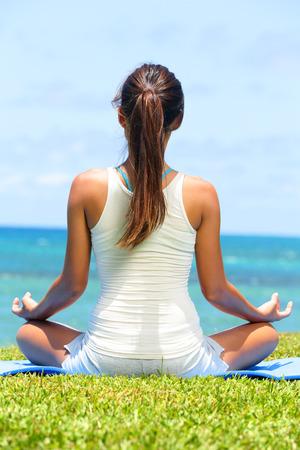 ビーチ背中とロータスの位置に座っている海洋の海で、瞑想に瞑想ヨガ女性は穏やかな、幸せになっています。アジアの女の子は、リラックスを楽しむ夏のビーチに座って。 写真素材 - 27940504