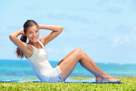 Fitness woman exercising doing sit ups outside during crossfit exercise training. Happy fit girl doing side crunches situps smiling happy. Beautiful mixed race Asian female model in grass by beach. Stock Photo