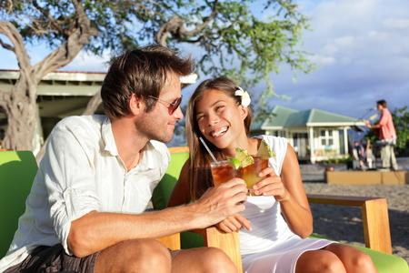 tomando alcohol: Dating divertirse bebiendo alcohol en el club de playa con la bebida alcoh�lica bebida Mai Tai c�ctel en Hawai. Retrato de rom�ntica pareja de j�venes de raza mixta en luna de miel rom�ntica en la playa de Hawai.