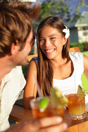 Romantic couple enjoying drinks at beach club talking smiling and laughing on Hawaii drinking alcoholic beverage Mai Tai cocktails. Lovers having fun together going out on vacation holidays. photo