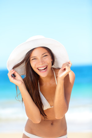 tanning: Beach woman happy on travel laughing cute enjoying sun tanning on travel smiling under blue sky.