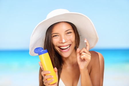 Sunscreen woman applying suntan lotion showing bottle.  photo