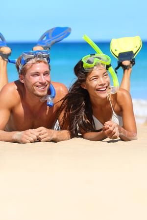 fin: Beach couple having fun snorkeling on vacation.