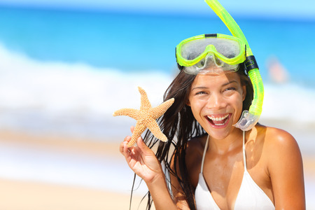 Beach travel woman with snorkel and starfish on vacation
