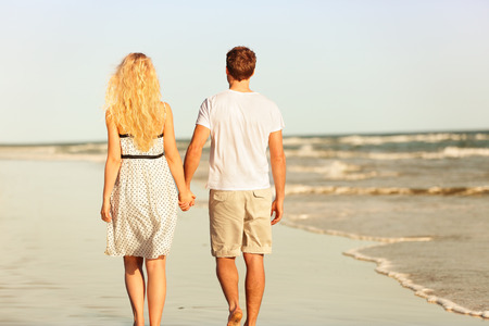 Beach couple holding hands walking at sunset by ocean sea.  photo