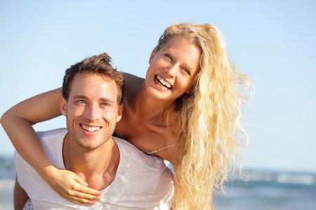 Beach couple fun - lovers on romantic travel doing piggyback in love on honeymoon vacation summer holidays romance. photo