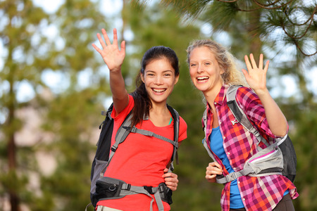 saying: Hiking women waving hello with hands smiling at camera happy during hike trek outdoors in forest.  Stock Photo