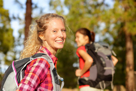 Hiking woman portrait smiling happy in forest.  photo