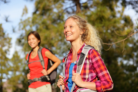 Active women - hiking girls walking in forest living healthy lifestyle doing outdoor activities.  Stock Photo
