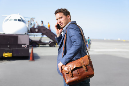 travellers: Airport business man on smartphone by plane.