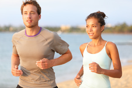 Running young pretty couple jogging on summer beach sand in sun. Exercising Caucasian fitness model and beautiful mixed race female sports model in 20s working out outdoors living healthy lifestyle. photo