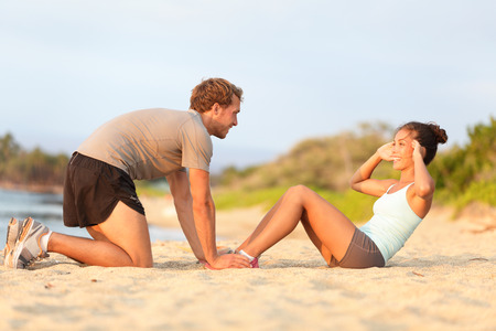 Fitness woman training situp crunches with personal trainer instructor. Young couple happy working out in sand on beach. Beautiful Asian female model and male fitness model holding her feet exercising Stock Photo