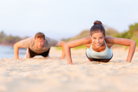 pushup: Fitness young people doing pushups on beach. Fit couple, female sport model and man training crossfit outdoors. Multiracial couple, Asian woman Caucasian man athlete in their 20s.