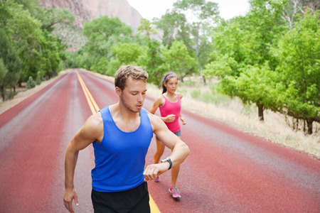 Runners training - young multiracial couple running exercising concentrated on road in beautiful nature. Caucasian fitness model man checking time or pulse on heart rate monitor watch.