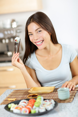 chopstick: Maki sushi. Healthy lifestyle woman about to eat sushi. Mixed race pretty young woman holding chopsticks smiling happily and cheerful. Full sushi plate in front