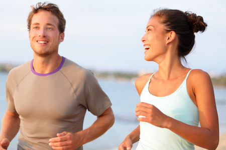 Jogging fitness young mixed race couple running happy smiling and laughing enjoying sports outdoors. Exercising multicultural people - young caucasian man and pretty asian model Stock Photo