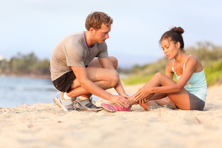 ankle: Injury - sports woman with twisted sprained ankle. Asian fitness female model sitting on beach sand getting help from Caucasian male touching her ankle.
